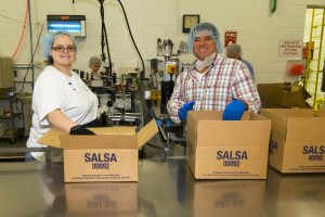 Shannon Tavis (l) and Alberto Enriquez, Liahona 5th Ward, Mesa Alma Stake, work as volunteers in Mesa's wet-pack cannery, where items, such as salsa, are canned with the Deseret label as part of the Church's worldwide efforts to help the poor and needy. Photo by John Power, Biltmore Photo.