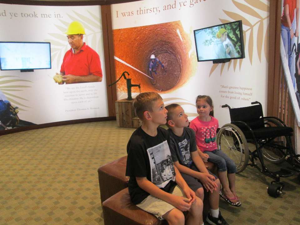"""Ethan Price, 10,  (l To R) And His Siblings, Colby, 8, And Sadie, 4, Are Among The Many Who Have Come As Family Groups, For Scout Outings Or For Young Men And Young Women Activities To See The """"Love Thy Neighbor"""" Display That Is Currently At The Mesa Temple Visitors' Center. Photo By Cecily Markland."""