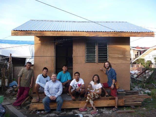 A Filipino Family Smiles In Front Of Their New House, One Of 10 Elevated Houses Built By David Carmichael (third From Left), His Son, Jace, (far Right) And Other Volunteers Who Helped With The Cleanup Efforts After Typhoon Yolanda Caused Mass Destruction In The Philippines.  Photo Courtesy Of David Carmichael