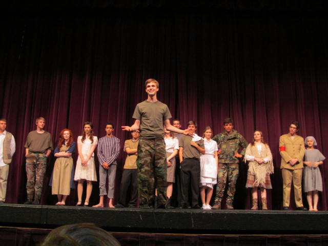 Surrounded by members of his high school drama club, Kyle Ellingson (front) takes center stage after the performance of the play Kyle wrote, called
