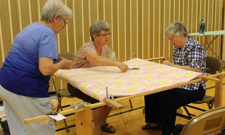Participating in the Mesa Alma Stake's evening of service that entailed completing projects found on JustServe.org, (left to right) Sisters Judy Van Tienderen, Joyce Boiyd and Barbara Stott work on a quilt for Project Linus.