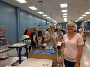 Young Women's leader, Cathy Bankhead (center, with broom) participates in a service project with Megan Trendler (r) and other Young Women at one of the packing sites for the non-profit organization Feed My Starving Children (FMSC). Photo by Laura Archibald