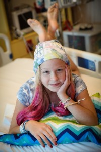 While battling leukemia, 11 year old Naomi Oakes, shown wearing one of her Happy Hair Bands, recognizes her own blessings and creates blessings for others. Photo by Shannon Oakes