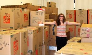 Haley Smith poses with one of the shipments in the Lifting Hands International warehouse. Photo by Scott Shipley