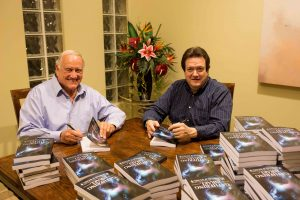 Co-authors John Wudel (left) and Michael Morton (right) sign copies of their book, Gathering Israel, which they say can strengthen testimonies with its message of Heavenly Father's love for all people. Photo courtesy of Michael Morton