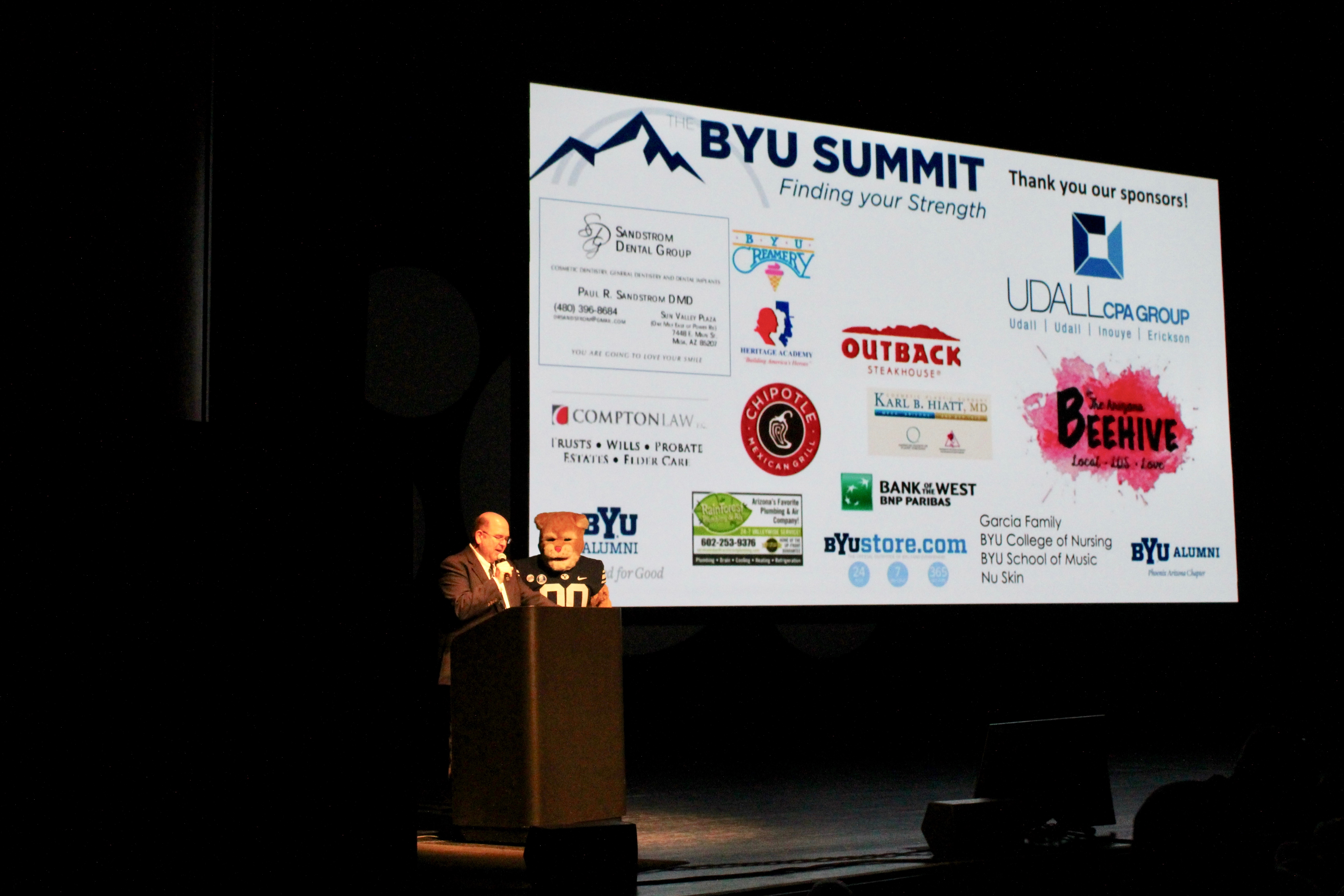Duane Oaks, Cosmo And Sponsor Screen on stage at The Summit. Photo by BYU Alumni Association.