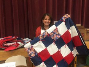 Jill Adair with a Red, White and Blue quilt made for the veterans. Photo courtesy of Jill Adair.