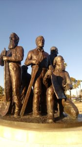 Shown holding a tool he used to help determine the grade needed to bring water to Mesa from an ancient canal, Francis Martin Pomeroy, center, one of the four founders of Mesa, is memorialized with the others—Charles Robson, George W. Sirrine and Charles Crismon—on a statue in Mesa's Pioneer Park. Photo by Cecily Markland Condie.