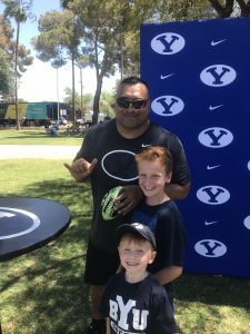 BYU Head Football Coach Kalani Sitake poses with some young fans.