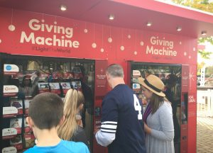 A missionary assists a family at the Giving Machines in Gilbert. Photo by Robin Finlinson.