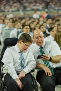 Father and his disabled son share a moment at the devotional. Photo courtesy of The Church of Jesus Christ of Latter-day Saints